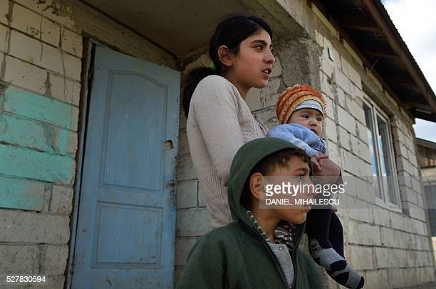 Year-old Diana holds her child next to her brother at their home in a village near Botosani, north-eastern Romania, on March 30, 2016. In 2013, 15.6...