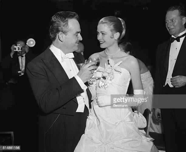 Lovely screen actress Grace Kelly and her fiance Prince Rainier III of Monaco toast each other during Imperial Ball at the WaldorfAstoria tonight The...