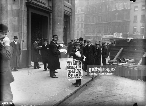 Newspaper boy Ned Parfett sells copies of the Evening News telling of the Titanic maritime disaster outside the White Star Line offices at Oceanic...