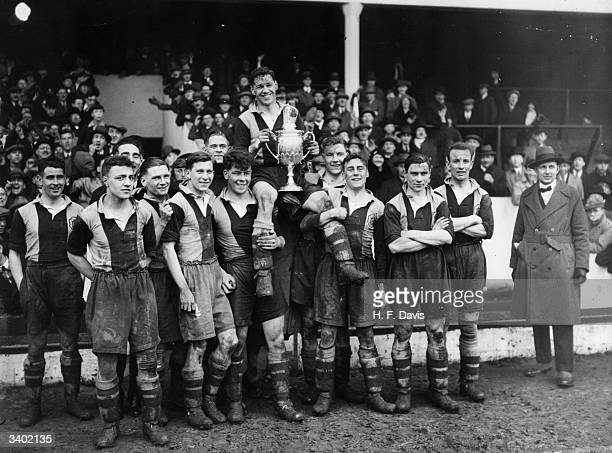 The players of Dulwich Hamlet amateur football club hold their captain and the trophy aloft after their victory over Marine in the Amateur Cup final...