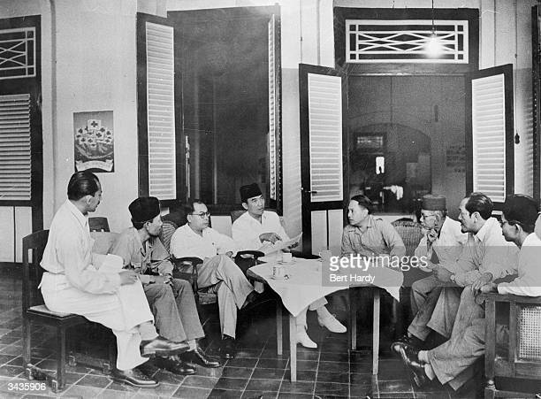 Sukarno selfproclaimed president of the Republic of Indonesia discusses with his cabinet a proposed conference with the Dutch government in the Hague...