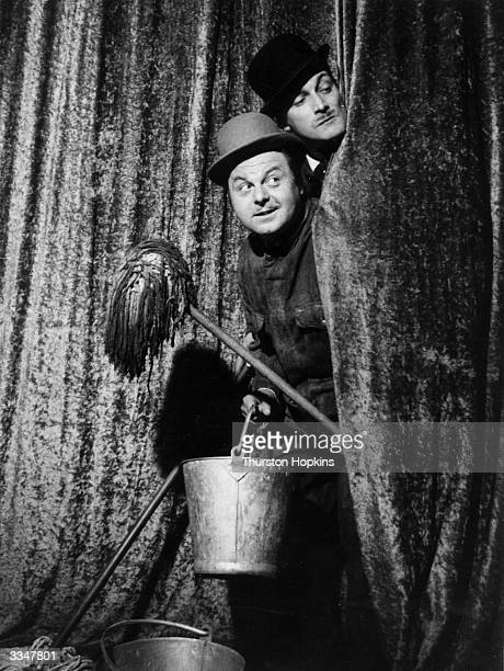 Lauri Lupino Lane and George Truzzi mischeviously peeping between the curtains with some comedy props Original Publication Picture Post 7668 Whatever...