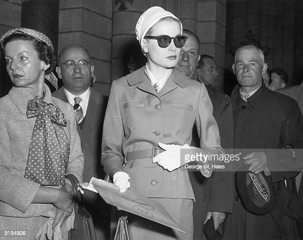 American actress Grace Kelly wearing sunglasses and a cloche hat during her wedding rehearsal at Monaco Cathedral