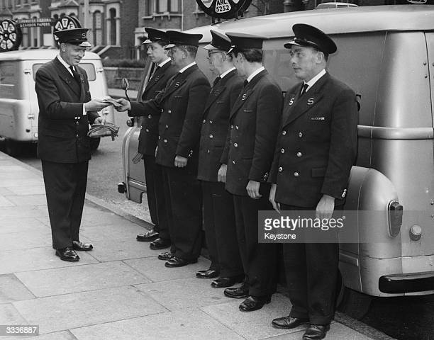 Bill Haines conducts the early morning inspection of uniformed staff at Satex Typecraft of Finsbury Park in London. Each day the men receive two...
