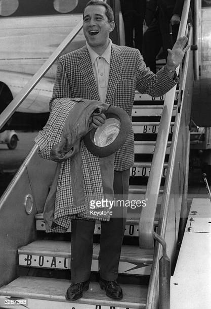 Perry Como , said to be the highest paid TV entertainer in the world, seranades a crowd of admirers who have gathered to greet him on his arrival at...