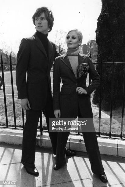 A man and a woman model a unisex suit