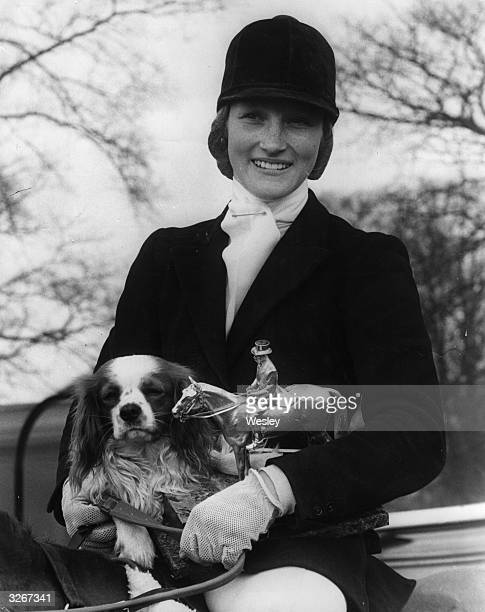 Lucinda Prior-Palmer, aged 19, the winner of the Badmington Horse Trials, pictured in her riding outfit with the trophy and her pet dog, 'Oliver'.