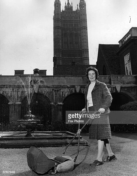 Head gardener of Westminster Abbey Marian Couchman mows the lawn of the little cloister
