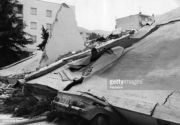 The rear of a car crushed under the ruins of the Court House in Montenegro pokes out from under the rubble