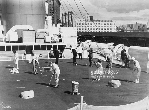 Men and women putt on a miniature golf course with artificial grass on the sun deck of the French Line's flagship SS Ile de France New York City