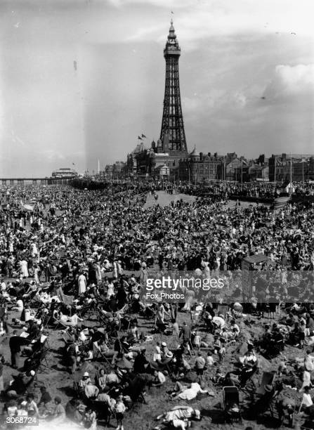 Crowds of holidaymakers lounging on the beach at Blackpool, with the famous Blackpool Tower in the background.