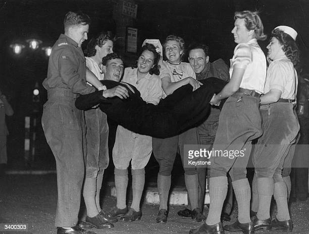 Sailor is thrown into the air and caught by a group of land girls in Trafalgar Square, London, during VJ Day celebrations.