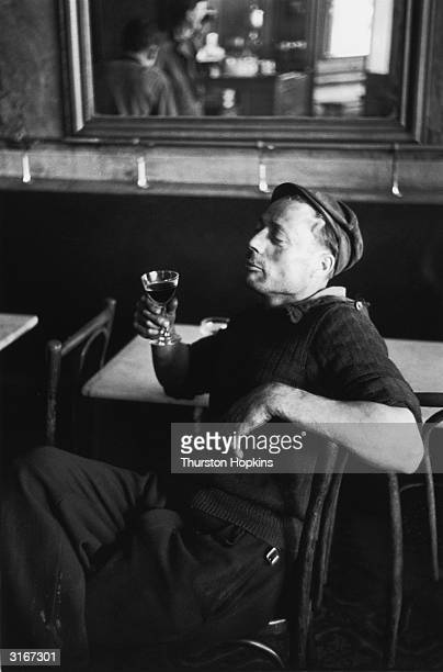 A workman savours a glass of red wine in a Paris bistro Original Publication Picture Post 6002 Paris Pride pub 1952