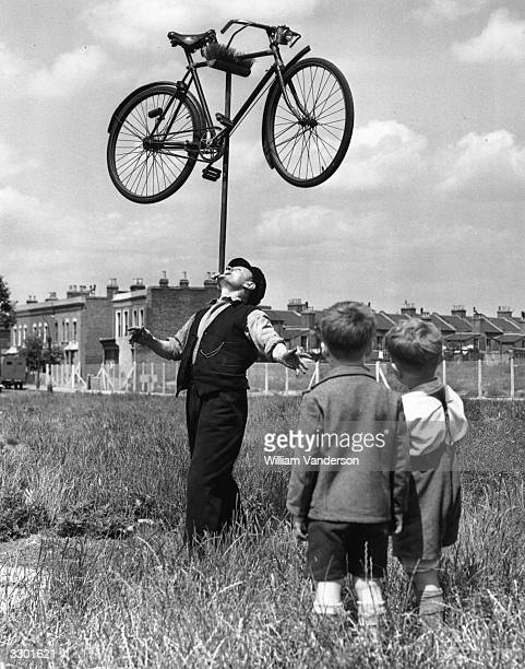 In the field outside his house in Plaistow East London 62yearold railway worker Mo Harris balances a bicycle on top of a broom on his chin watched by...