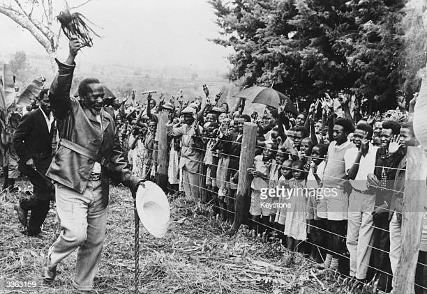 Kenyan politician Jomo Kenyatta waving to a crowd of wellwishers on arrival at Nairobi Kenya following his release from years of detention and exile