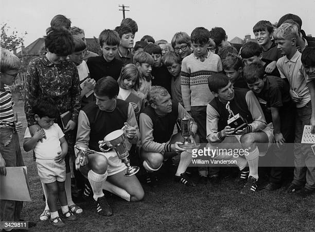 Crowd gathered around the three West Ham players, Geoff Hurst, Bobby Moore and Martin Peters, who played in the England team which won the World Cup....