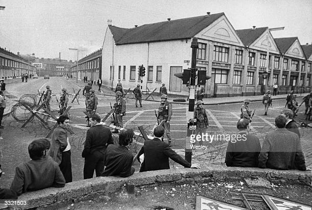 Residents watch British troops guarding the entrance of the Falls Road area, behind barbed wire barricades, at Belfast after shootings.