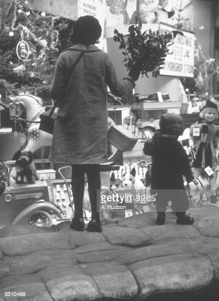 Two children standing on sandbags in order to look at Selfridge's Christmas window
