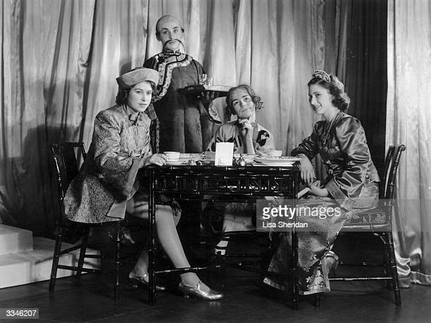 Queen Elizabeth II Princess Margaret and two other cast members performing the tea party scene in a production of 'Aladdin' at Windsor Castle...