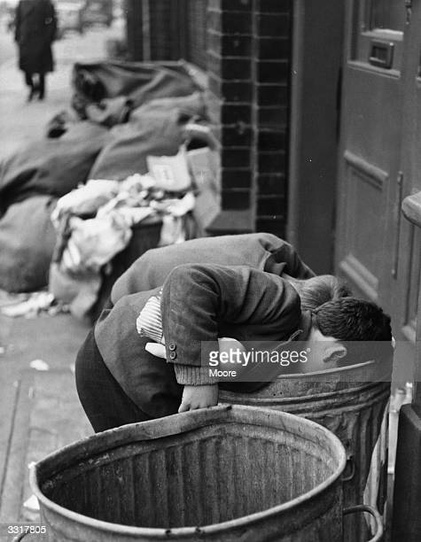 Two boys search the bins outside a toy shop in the hope of finding a 'bargain' One boy has already found a broken doll