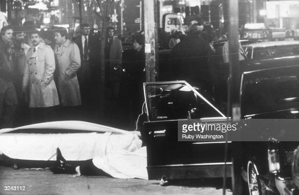 View of the body of American criminal Paul Castellano covered with a sheet after he was gunned down on the sidewalk of E 46th St New York City
