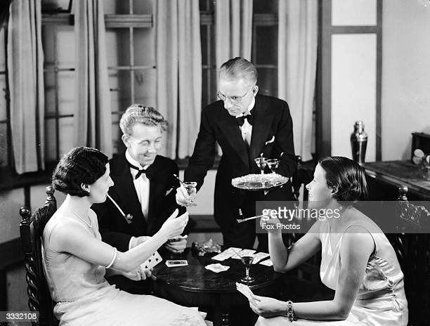 A butler serves cocktails to two elegant pipe smoking women Vera Richardson and Miss Brown who are playing cards with Fox photographer Fred Morley