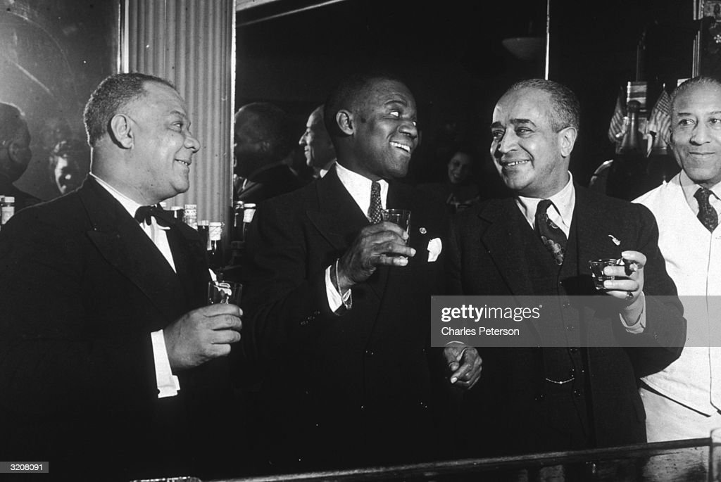 American jazz clarinetist Sidney Bechet (1897 - 1959) and American dancer Bill 'Bojangles' Robinson (1878 - 1949) join the owner of the Mimo Club for a drink between sets, Harlem, New York City. Bechet was in residency at the Club.