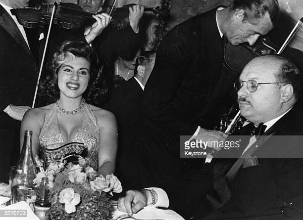 Violinists serenading exKing Farouk of Egypt with his latest female companion Miss Naples 18yearold Irma Minutolo at a Monte Carlo casino