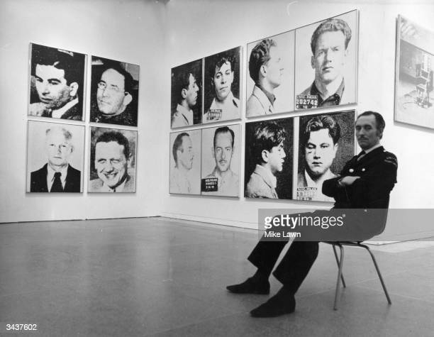 A security guard at the Tate Gallery London where Andy Warhol's series of portraits entitled 'The Most Wanted Men' are being shown