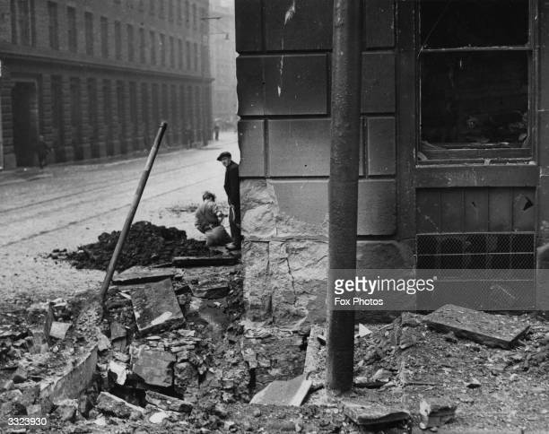 A couple of men working near the crater where an IRA bomb exploded in Manchester killing one man and dislocating all transport gas electricity and...