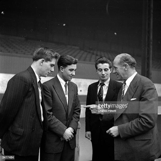 Manchester United manager Matt Busby talking to a group of young footballers at Old Trafford Manchester Busby born in Orbiston Lanarkshire started...