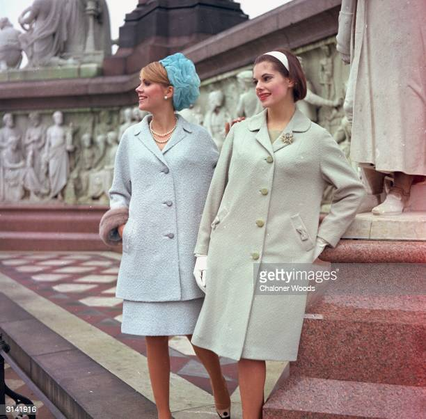 Tulle pillbox hat worn with a pale blue suit with threequarter jacket the sleeves are edged with fur Her companion is wearing a pale green loose...