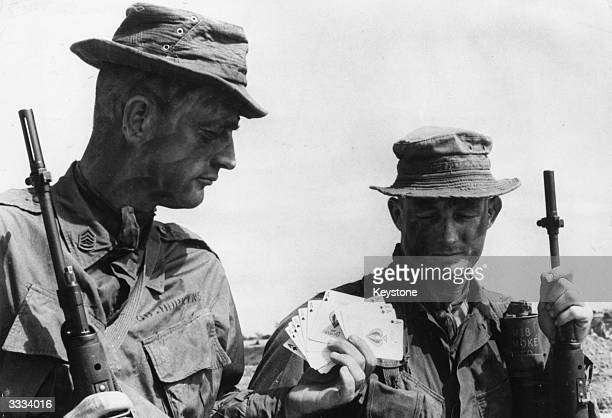 Two US Marine sergeants getting a supply of Ace of Spades cards known as the 'death cards' which the reconnaissance forces leave as a warning to the...