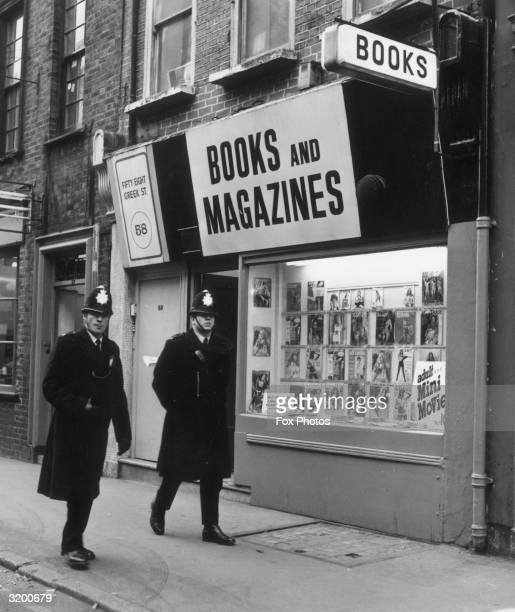 Two policemen walk past a bookshop selling pornographic material in Greek Street Soho London