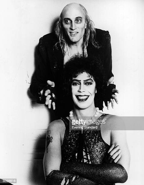British actor Tim Curry seated poses with Richard O'Brien his costar in the cult musical 'The Rocky Horror Picture Show' and author of the original...