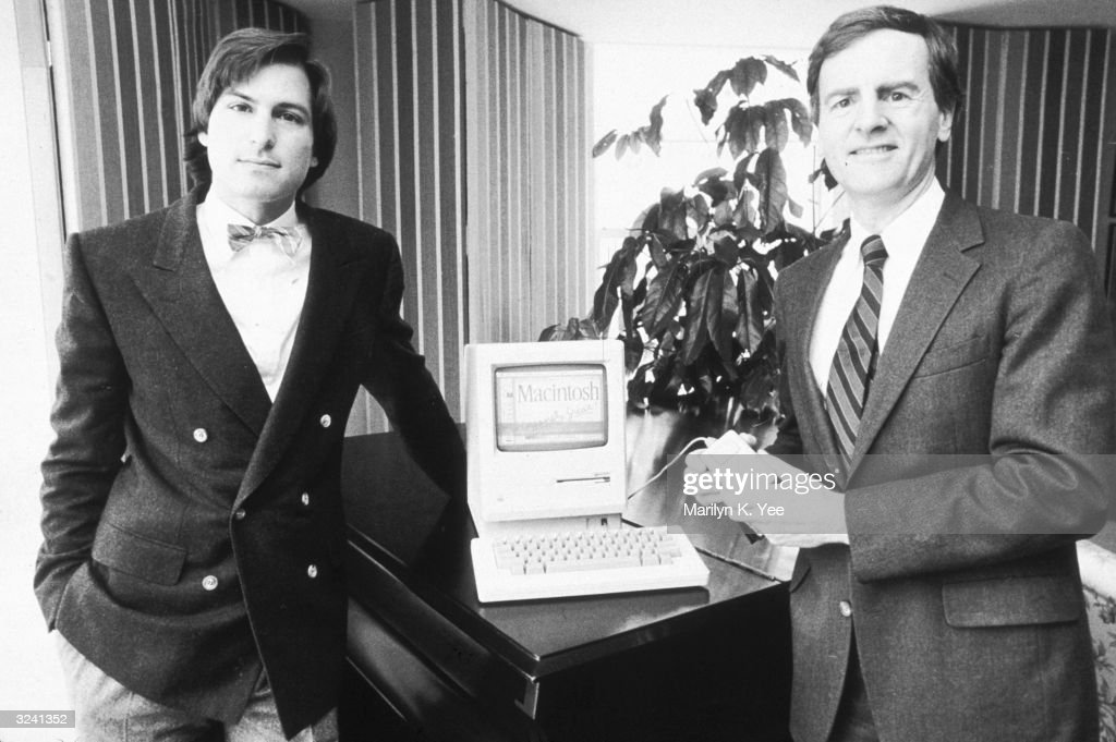 American businessman Steve Jobs (L), Chairman of Apple Computers, and John Sculley, Apple's president, pose with the new Macintosh personal computer, New York City.
