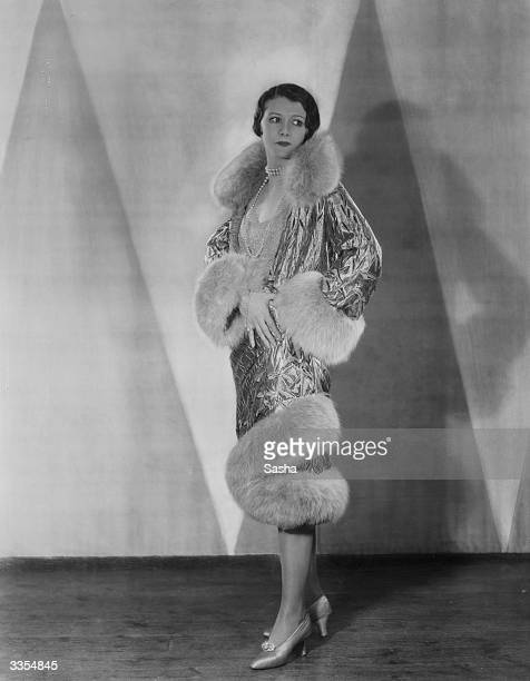 British film star Isabel Jeans models a luxorious evening coat lavishly trimmed with fur at neck wrist and hem She was the wife of actor Claude Rains