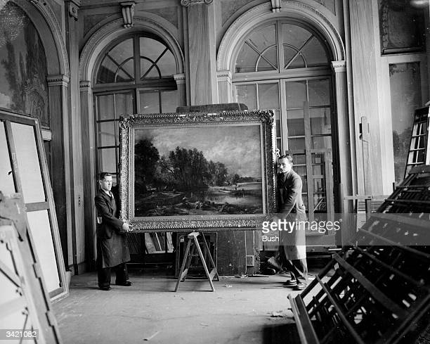 Two gallery assistants holding John Constable's 'Stratford Mill' which sold at Christie's auction house for forty one thousand guineas