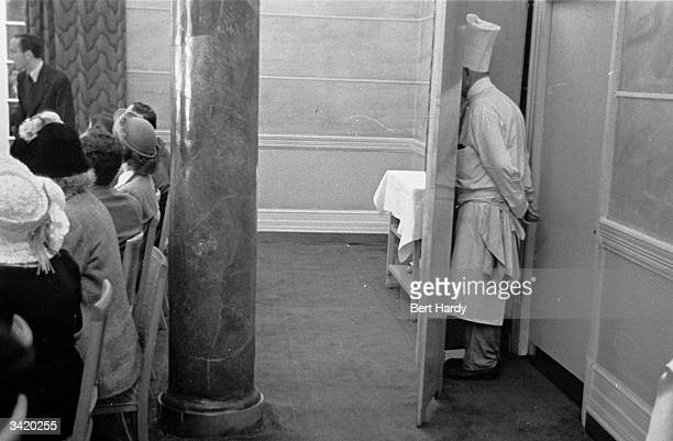 A Hotel chef watches proceedings from behind a screen at the back of the room as German screen actress Marlene Dietrich gives a press conference at...