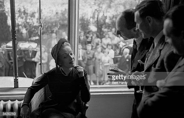German screen star Marlene Dietrich grants an audience to some avid British journalists at the Savoy Hotel, whilst in London for the filming of...