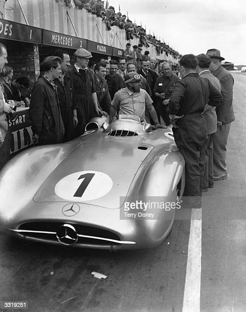 Argentine racing driver Juan Manuel Fangio getting out of his Mercedes after setting a new lap record at 10035 miles per hour during a practice run...