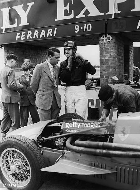 British racing driver Mike Hawthorn in the pits with his Ferrari during preparations for the British Grand Prix at Siverstone.