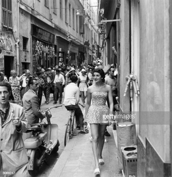 A fashion model roams the streets of San Remo wearing her shortest dress during a cruise around the Cote d'Azur to introduce the latest British...