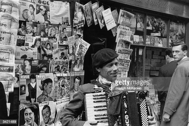 An accordion player busking outside a magazine stall in London's Soho Original Publication Picture Post 7855 Soho London's Little Europe pub1955