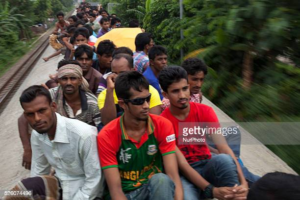 Bangladeshi Muslims make space for themselves on the roof of an overcrowded running train to head home ahead of Eid alFitr as others wait at a...