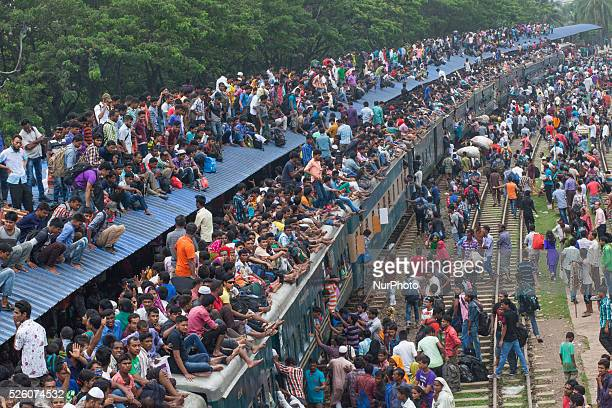 Bangladeshi Muslims make space for themselves on the roof of an overcrowded train to head home ahead of Eid alFitr as others wait at a railway...