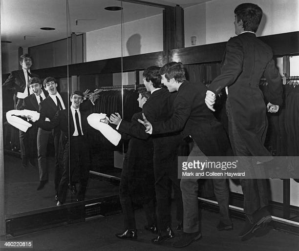 The Beatles pose wearing morning coats in front of a full length mirror at the Austin Reed store in Regent Street London on 16th July 1963 Left to...