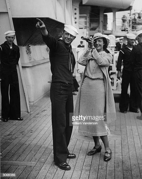 A sailor on the US cruiser 'New Orleans' points out objects of interest to a telescopeusing visitor The cruiser is on a visit to Portsmouth