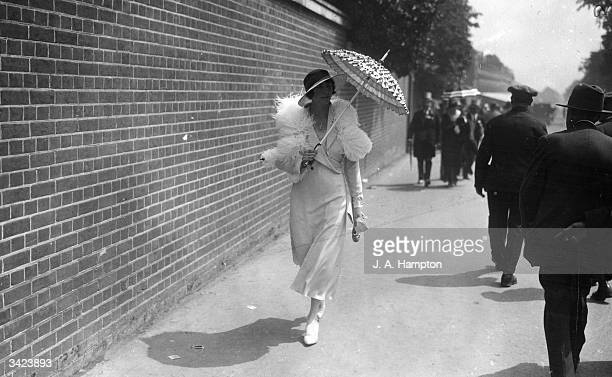 Using a parasol to shelter from the sun on the third day of the races at Ascot