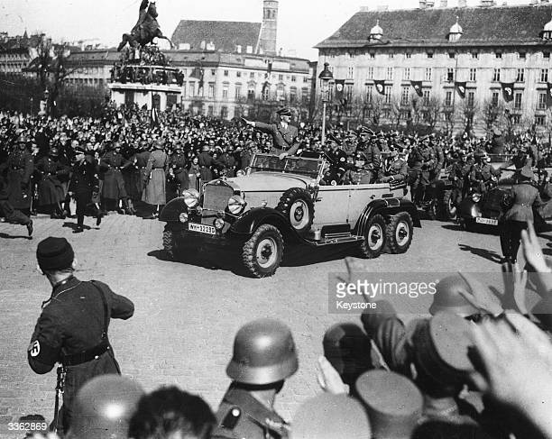 German dictator Adolf Hitler during his Victory Parade following the German invasion of Austria He acknowledges the cheers by saluting from his car